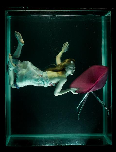 Vrouw in water met een rode stoel Gratis Foto
