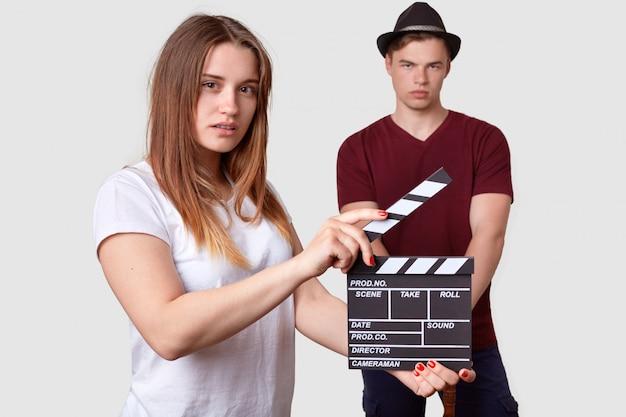 Vrouw in wit t-shirt houdt klepel boord, schiet scène, serieuze stijlvolle man staat op de voorgrond, draagt stijlvol hoofddeksel en t-shirt, betrokken bij filmproductie. film maken concept Gratis Foto