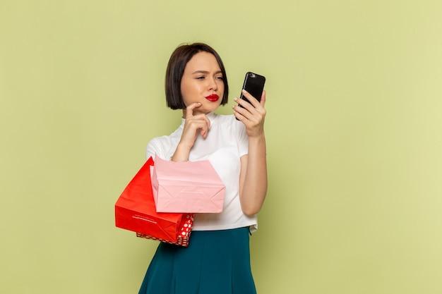 Vrouw in witte blouse en groene rok met winkelen pakketten en telefoon Gratis Foto