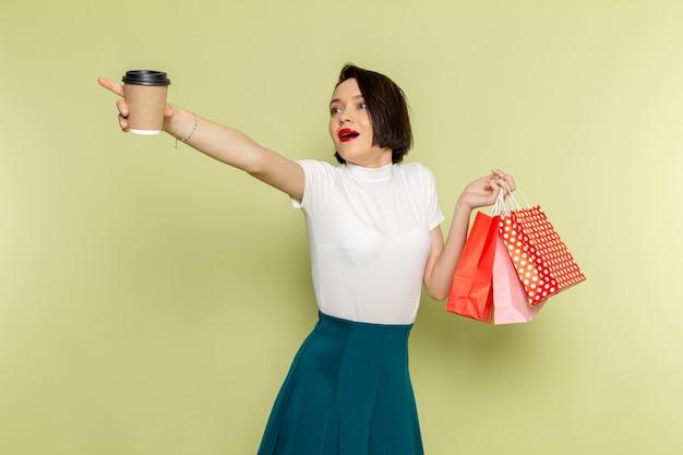Vrouw in witte blouse en groene rok shopping pakketten en koffie te houden Gratis Foto