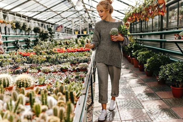Vrouw in witte gympen, grijze baggy outfit loopt door plantenwinkel en houdt cactussen in haar handen. Gratis Foto