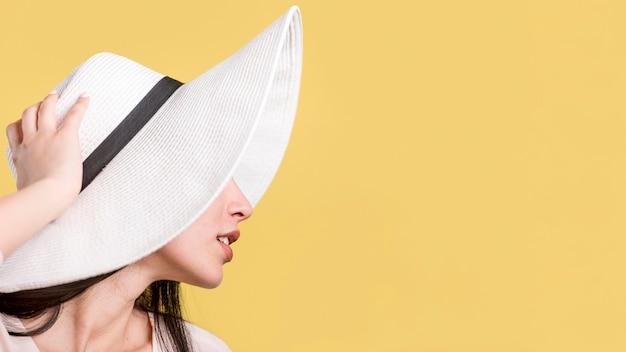 Vrouw in witte hoed op gele achtergrond Gratis Foto