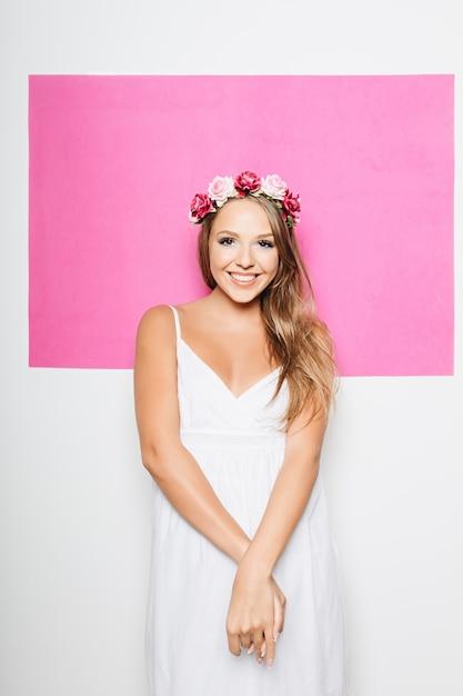 Vrouw in witte katoenen kleding met bloemen in haar het glimlachen Gratis Foto