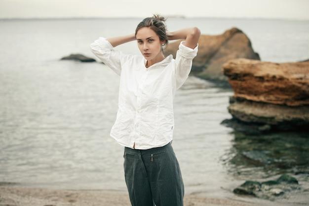 Vrouw in witte kleding repareert haar. Premium Foto