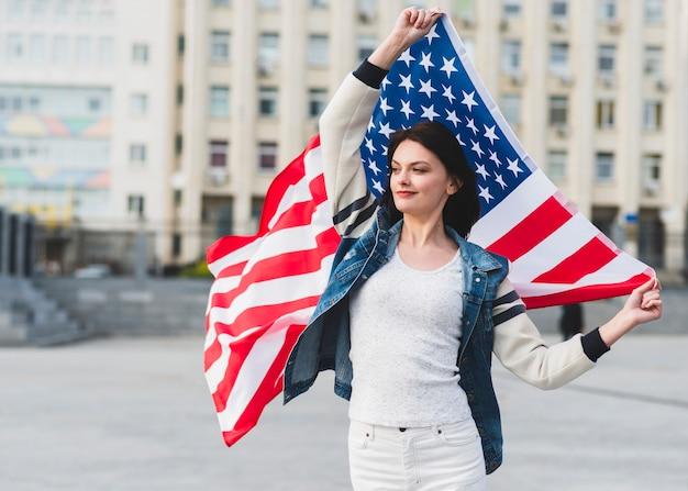 Vrouw in witte kleren met amerikaanse vlag op straat Gratis Foto