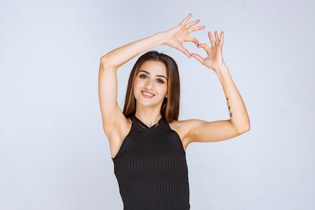 Vrouw in zwart overhemd die het teken van de harthand doen. Gratis Foto