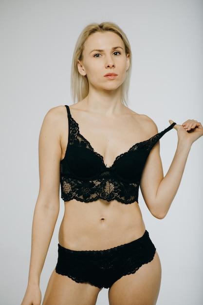 Vrouw in zwarte lingerie die op wit wordt geïsoleerd Premium Foto