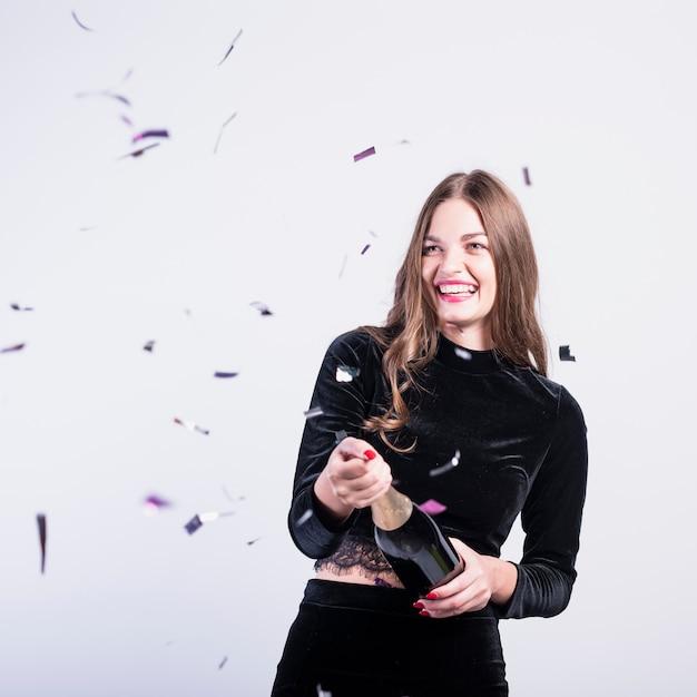 Vrouw in zwarte opening champagnefles Gratis Foto