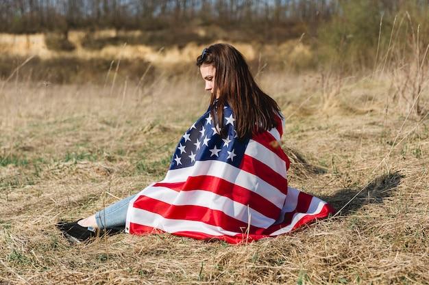 Vrouw inwikkeling in de vs vlag op 4 juli Gratis Foto