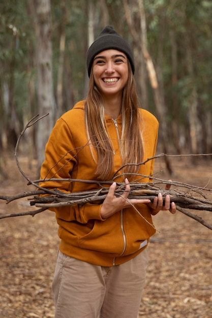 Vrouw kamperen en hout verzamelen Premium Foto