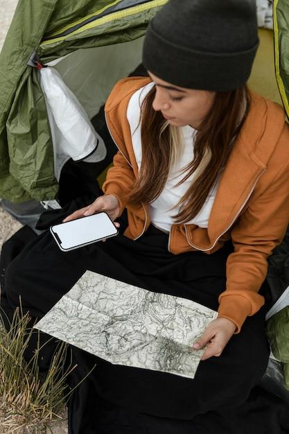 Vrouw kamperen en kijken op de kaart hoge weergave Gratis Foto