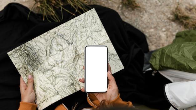 Vrouw kamperen en kijken op het bovenaanzicht van de kaart Gratis Foto