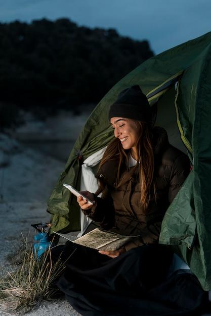 Vrouw kamperen en met behulp van mobiele telefoon Gratis Foto