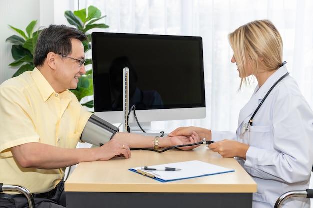 Vrouw kaukasische professionele arts controleren bloeddruk met patiënt in het ziekenhuis kamer. Premium Foto