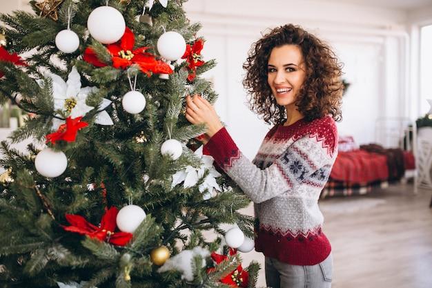 Vrouw kerstboom versieren Gratis Foto