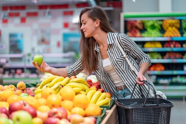 Vrouw kiest vers fruit in de supermarkt. klant het kopen van voedsel in supermarkt Premium Foto