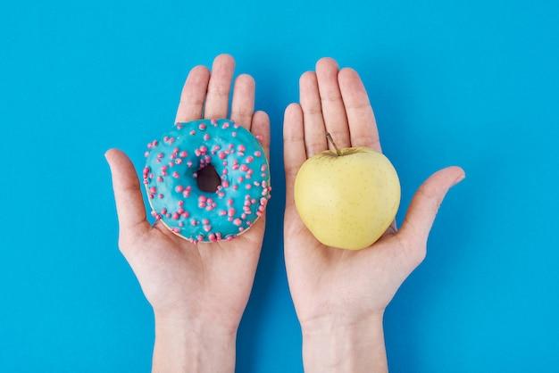 Vrouw kiezen tussen appel en donut in haar handen. gezond eten concept. Premium Foto