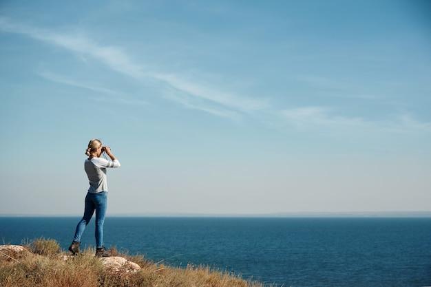 Vrouw kijkt door een verrekijker Gratis Foto