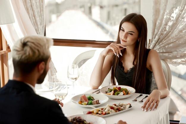 Vrouw kijkt hartstochtelijk op een knappe in het restaurant Gratis Foto
