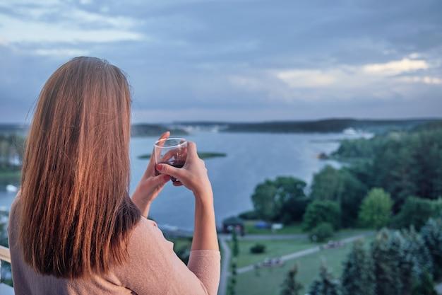Vrouw kijkt 's avonds naar de zee van minsk Premium Foto