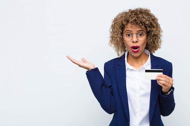 Vrouw kijkt verbaasd en geschokt, met open mond, met een open hand opzij Premium Foto