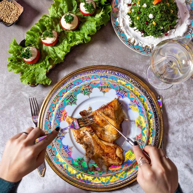 Vrouw kip maaltijd eten op de tafelblad-weergave Premium Foto
