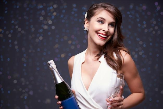 Vrouw klaar om champagne te gieten Gratis Foto