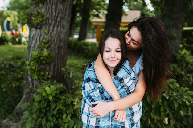 Vrouw knuffel meisje verpakt in geruite plaid Gratis Foto