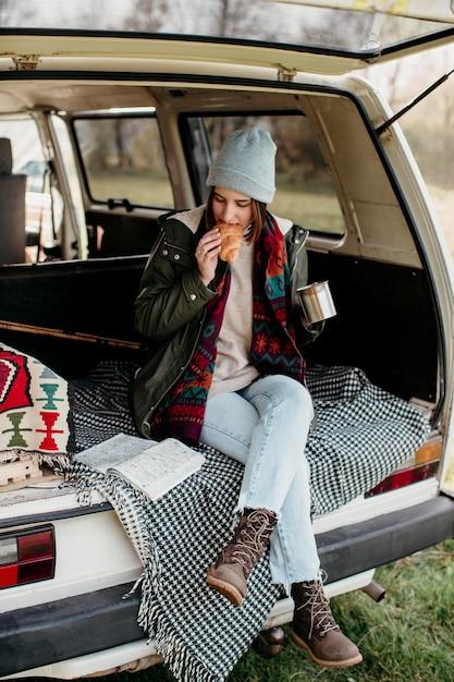 Vrouw koffie drinken en een croissant eten in een busje Premium Foto