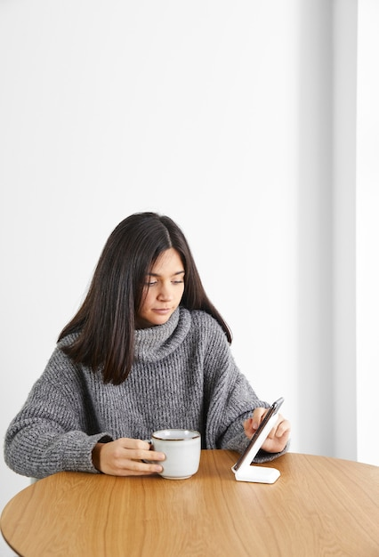 Vrouw koffie drinken tijdens het gebruik van telefoon Premium Foto