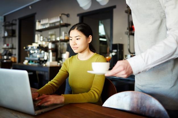 Vrouw koffie of thee drinken tijdens het werken op de laptop Gratis Foto