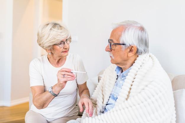 Vrouw koorts temperatuur van senior man zittend op bed controleren Premium Foto
