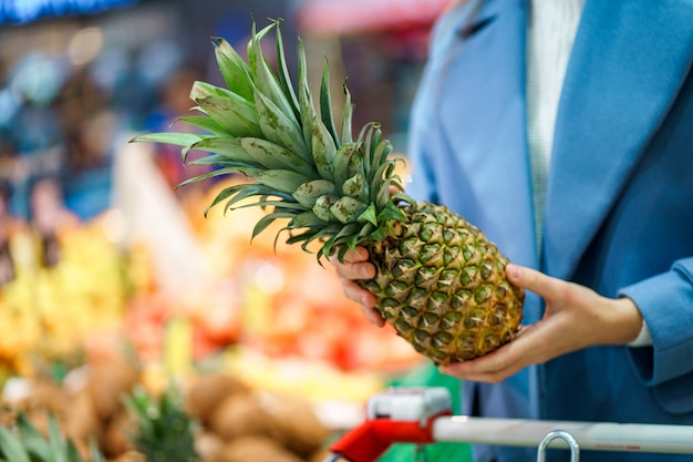 Vrouw koper met kar in de supermarkt tijdens het kiezen en kopen van verse ananas op fruitafdeling Premium Foto
