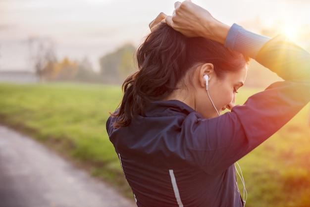 Vrouw koppelverkoop haar in paardenstaart klaar om te oefenen bij zonsondergang Premium Foto