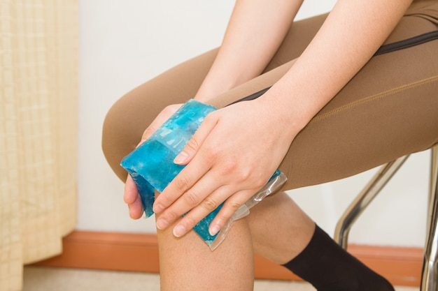 Vrouw koude pak toe te passen op gezwollen pijn knie na sportblessure Premium Foto