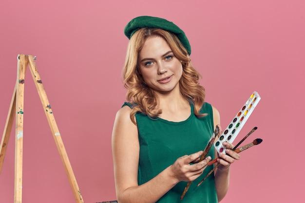 Vrouw kunstenaar groene baret aquarel penseel puttend uit een roze achtergrond Premium Foto