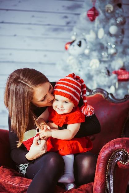 Rode Lederen Fauteuil.Vrouw Kust Haar Dochter Zittend Op Rode Lederen Fauteuil Foto