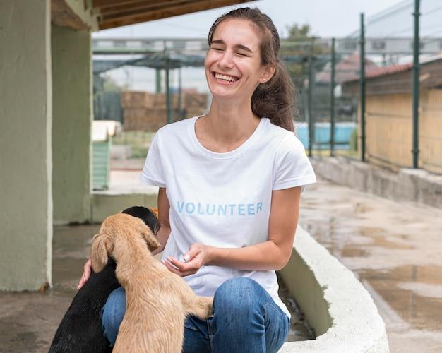 Vrouw lacht tijdens het spelen met reddingshonden in het asiel Premium Foto
