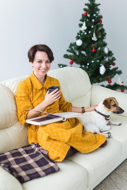 Vrouw leest boek voor kerstboom met hond jack russell terrier. kerst, feestdagen en Premium Foto