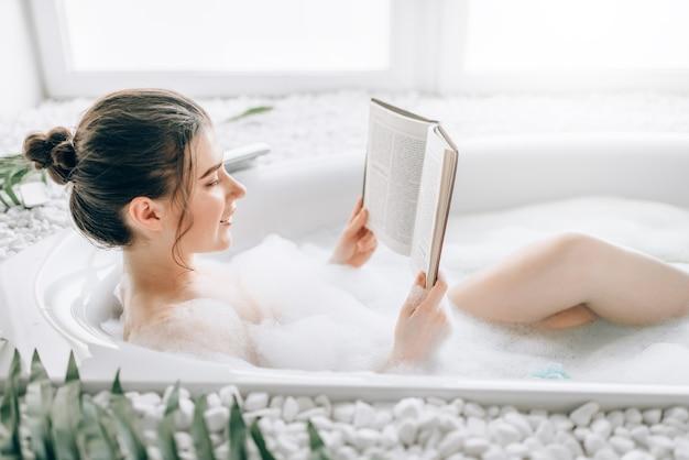 Vrouw liggend in bad met schuim en tijdschrift leest Premium Foto