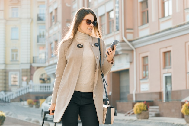 Vrouw loopt langs stadsstraat met reiskoffer en mobiele telefoon Premium Foto