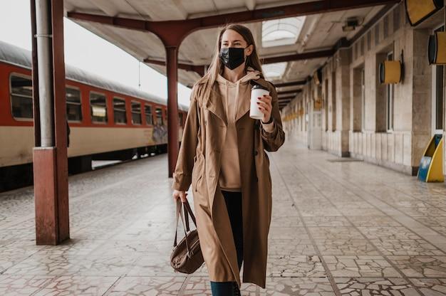 Vrouw lopen met een kopje koffie in een treinstation Gratis Foto