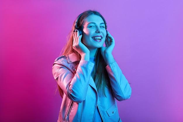 Vrouw luistert naar muziek op koptelefoon genieten van favoriete liedjes, houdt de ogen gesloten, gelukkig lachen Premium Foto