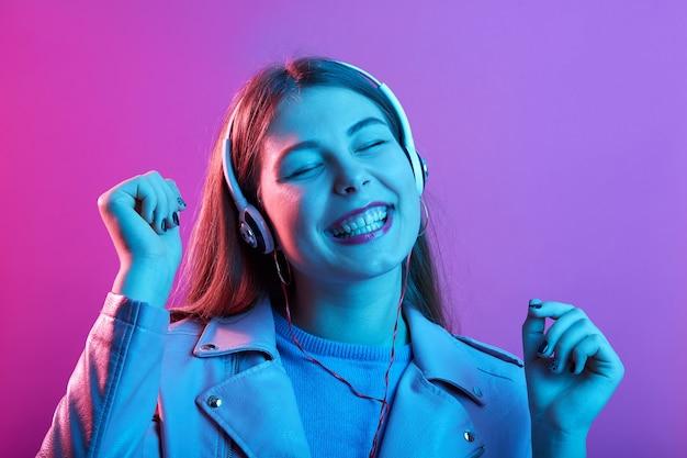 Vrouw luistert naar muziek via koptelefoon, houdt de ogen gesloten en blij lachend, met vuisten omhoog geïsoleerd boven roze neonruimte Premium Foto