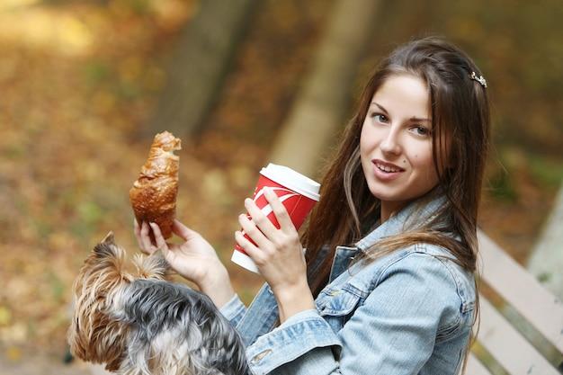 Vrouw lunchen tijdens een wandeling met haar hond Gratis Foto