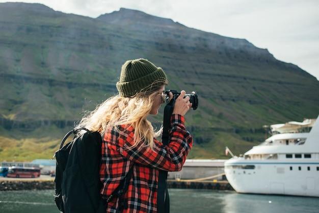 Vrouw maakt foto's van episch cruiseschip in fjord Gratis Foto