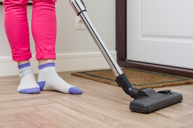 Vrouw maakt schoon met behulp van stofzuiger Premium Foto