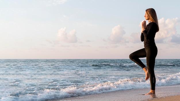Vrouw mediteren op het strand met kopie ruimte Gratis Foto