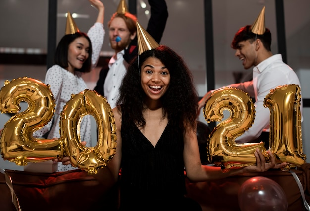 Vrouw met 2021 ballonnen op feestje Gratis Foto