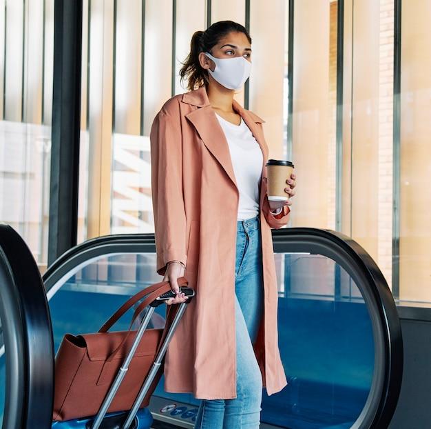 Vrouw met bagage en medisch masker op de luchthaven tijdens de pandemie Gratis Foto